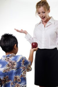 Student giving a teacher an apple
